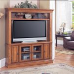 Wooden-corner-TV-cabinet-with-additional-upper-shelf-in-modern-rustic-style-a-big-flat-TV-classic-area-rug-wood-floors-idea-an-arm-chair-with-black-stained-wood-side-table-with-table-lamp-