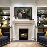 charm living room design with flat screen tv on white mantel fireplace between square twin grey couches with yellow cushions 1