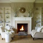 enamor living room design with twin beige couches near craving mantel fireplace and zebra side table with beige barrel decoration