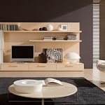 minimalist living room design with cream polished round plywood coffee table using steel leg on dim gray rug as well as beige lounge chair also wooden tv rack stand built in wall cabinets as well as p 938x49